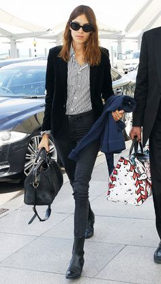 Alexa Chung wears a striped button-down blouse, black blazer, skinny jeans, chelsea boots, and a suede duffle bag