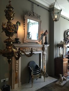 A world where antiques meet reproduction and works of art from nature. Our image shows the reproduction Cheere fireplace with an antique chandelier lantern and taxidermy from Darwin, Sinke & vom Tongeren.