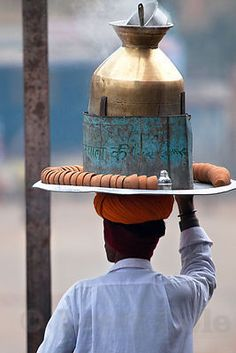 A mobile tea vendor with his livelihood on his head - a brass urn with hot tea and earthenware clay pots