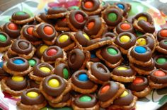 Just melt Hershey's kisses onto tiny twist pretzels (275 degrees, 3 minutes), remove, and immediately press a single m&m on each. Refrigerate until eating to make sure they are deliciously solid!