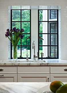 We love this look! Kitchen Designer Mick De Giulio lowered the windowsills to make them level with the countertops and let in more light. - Traditional Home ®/ Photo: Dave Burk / Design: Mick De Giulio