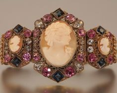 """This rare and beautiful bracelet is an exquisite find! The gilt wash sterling bracelet is set with hand carved shell cameos surrounded by glass and paste stones in clear, pink and sapphire blue. The bracelet is seven inches long and the centerpiece is 2"""" by 1 1/4"""". The bracelet has a tight clasp with safety chain. Probably Czechoslovakian in origin. Circa 1840."""