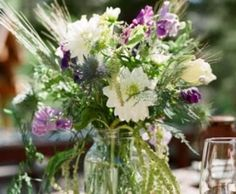 A mason jar filled with seasonal greenery, lavender spray roses, white wax flower, purple lilac, lavender scabiosa, and queen anne's lace will accent the guestbook table