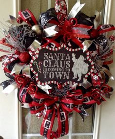 This is a Christmas wreath made from black deco mesh. It is wrapped in silver ribbon. It is accented with 5 coordinating black, red, white and silver ribbons. Ribbon centers are decorated with ornaments, red curly cues and silver twigs decorated with red ornaments. 13 x 9 metal chalkboard sign with Santa Claus is coming to town adorns the center. Attached ribbon for hanging.