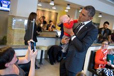 On This Day: President Obama holds a baby while greeting patrons at The Coupe restaurant in Washington, D.C., Jan. 10, 2014 (Photo by Pete Souza)