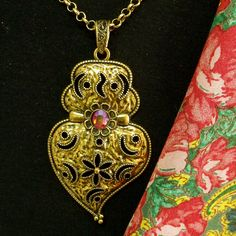 Portuguese folk Heart of Viana style Gold tone pendant jewelry necklace. Composition made by me with addition of Red Swarovski rhinestone and inspired in the traditional jewelry used by country women in Minho, in the north of Portugal. $39.00...#portugaljewelry#heartofvianapendant#madeinPortugal#portuguesejewelry#goldheartpendant#vianaheartnecklace#portuguesefolkjewelry