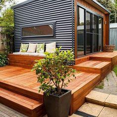 Casa compacta com acabamento e piso em madeira, portas de correr com esquadria em alumínio preto.