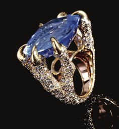 SAPPHIRE AND DIAMOND RING, MONTURE CARTIER The mount pavé-set with brilliant-cut diamonds designed as a pair of bird claws clutching a cushion-shaped sapphire, mounted in yellow gold, inscribed Monture Cartier.