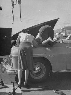 Girl attendant looking for battery for customer.   ( Los Angeles, CA, US  /    October 1948 ) by 	Allan Grant