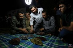 In this Tuesday, July 7, 2015 photo, Kurdish men discuss which hat to pick up while playing a game of Klawane in Irbil, Iraq. The traditional Iraqi Kurdish game is only played after Iftar during Ramadan. Two teams of four compete, where one team hides a ring in a traditional hat. The other team has to guess in which hat the ring is hidden. The team that hides the ring scores points for each hat that is leftover after the other team finds the ring. (AP Photo/Bram Janssen) The Allure, July 7, Iftar, One Team, Ramadan, Scores, Tuesday, Hat, Traditional