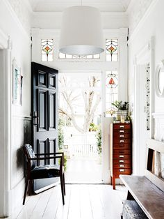 All-white entryway with black front door, stained glass around door frame and single chair
