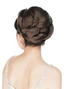 """高貴な魅力を最大限に引き出す夜会巻きで、存在感あるティアラを際立たせて。上下のパートに分けた下の髪につけ毛を加えて、""""の""""の字に巻き込みなが..."""