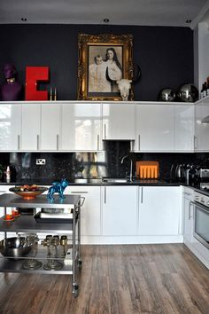 Love the drama & the way it makes the white cabinets stand out. Fantastic gilt frame against more casual modern features too
