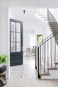 Sleek wrought iron staircase spindles and handrail with gray wash treads in a fo. Sleek wrought iron staircase spindles and handrail with gray wash treads in a foyer boasting ivory and black floor tiles complementing a black front door. Staircase Spindles, Metal Stair Railing, Wrought Iron Staircase, Staircase Design, Railings, Iron Balusters, Spiral Staircases, Banisters, Home Interior