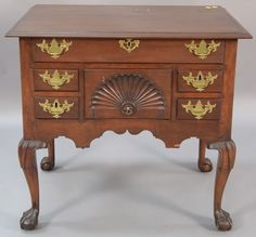 Nadeau's Auction Chippendale mahogany lowboy having rectangular top over one long drawer over central shell carved deep drawer flanked by two small drawers on either side with carved apron, all set on carved cabriole legs ending in ball and [...more]