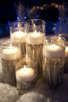 White wood branches under water. Could be artificial or not. Fill with water. I do not think the candles need to be floating ones. The branches might be able to hold them up and keep them stable.