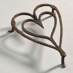Wrought Iron Heart-shaped Trivet, America, late 18th, early 19th century. Shaped as a heart within a heart, resting on three feet.