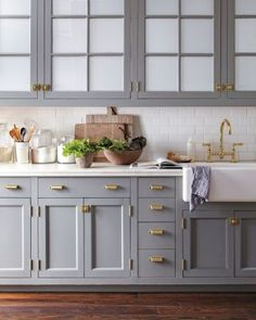 gray cabinets, marble countertops, brass hardware and plumbing fixtures