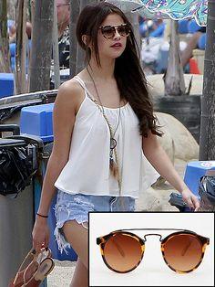 SELENA GÓMEZ  Selena siempre acierta con ropa y accesorios modernos y cool, como es el caso de estas gafas, que últimamente son sus favoritas. ¿Eres fan del estilo de la estrella juvenil? Pues estos lentes de sol de Urban Outfitters son ideales para ti, y lo mejor es su precio de solo $16.