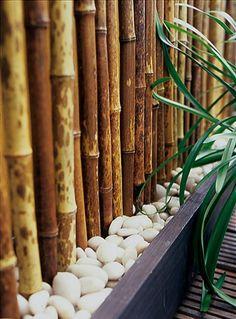 Selbstgemachter Balkon-Sichtschutz mit Blumenkästen, großen Kieseln und Bambusstangen