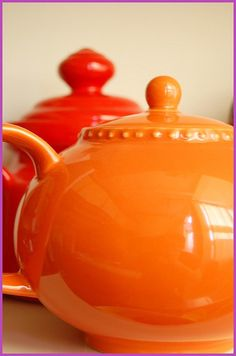 Two earthenware teapots -- one an orange-yellow; the other orange-red. Photo by Tricia Royal