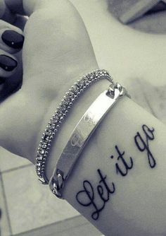 "Little wrist tattoo saying ""Let it go""."