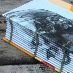 """By carefully wrapping the same image, moving it slightly, the face appears on the spine. From """"My Handbound Books"""". Awesome"""