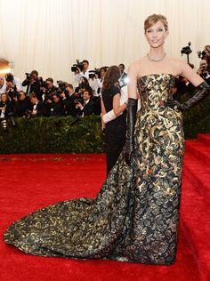 Karlie Kloss, com vestido Oscar de la Renta tomara que caia bordado de dourado e luvas de couro