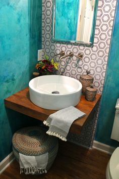 This bold teal powder room features a floating wood countertop, round basin sink and a white patterned accent wall to break up the rich, textured wall color.