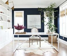 Home decorating ideas - crisp and clean high style home office with dark blue accent wall, cowhide rug, white painted builtins and gold accents.  Follow link for best paint color trends to try in 2016. We're sharing our favorite paint colors of the year, from blues and greens to whites and grays.