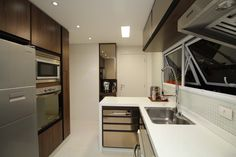 Cozinha super moderna com bancada branca, portas em espelho bronze. Projeto da arquiteta e designer de interiores Pricila Dalzochio. www.priciladalzochio.com.br