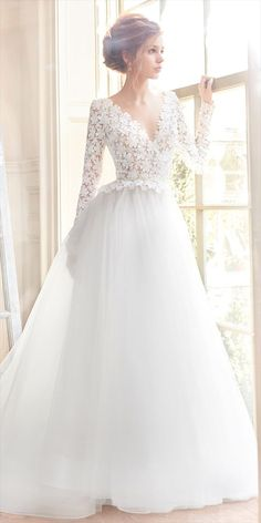 Ivory sparkle tulle bridal ball gown, Long sleeve Venise lace bodice with cashmere lining and V neckline, Scalloped peplum detail with ribbon accenting the natural waist, deep V back, Tulle skirt with horsehair hem detail and chapel train.