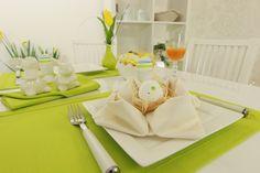 Schöne Stoffserviette auf einer frühlings grünen Tischdecke für Ostern dekoriert.