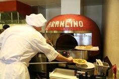 「アランチーノ・アット・ザ・カハラ」では、お店の中央にディスプレイキッチンを設置!調理そのものが一つのショーと化す。味覚だけでなく、視覚、聴覚、五感全てで味わう事が出来るさまは、まさにエンターテイメント。その奥に鎮座するピザ釜は本場イタリアからわざわざ取り寄せた本格的なもの。