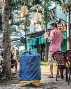 "With the gentle care usually afforded small children a man tends to his birds on a corner in District 10 where a group of men gather in the mornings to drink coffee and chat. ""Come sit down and join us sister"" a man at another table says noticing my curiosity. ""What do you want? I'm getting you a coffee! You'll have one with us won't you"" he states more than asks. I've just had a huge cup of warm sugared soy bean milk while chatting with a street vendor so I tell him I'd love a bottle of…"