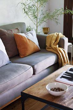 Living moderno en un depto chico de un edificio inglés, ambientado con muebles de madera y textiles naturales. De los responsables del estudio Pennsylvania Interiorismo.