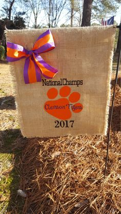 Clemson Tigers National Champs! CELEBRATE! Clemson Tigers burlap garden flag. Design is original and is embroidery/applique. Fabric/bow may differ slightly from photo. Flag has been treated with water repellent spray so although not waterproof it will be good in the weather. Measures apx 13 in wide by 18 in long. One photo shows that this flag is double and the backside of the design is not visible. (This flag fits a small garden flag pole which is not included.)  If you have questi...