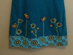 I added 3D flowers to my granddaughter's jumper by fusing the flower print to a plain background, then using coordinating threads (metallic blue for a bit of sparkle and a shiny brown) I satin stitched around the flowers, cut them out, then gathered them slightly and sewed them to the dress using coordinating buttons as the center of the flowers.  Cute, easy way to add dimension to the jumper, but will wash well and endure the life of a first grader!