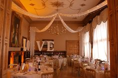 Orchardleigh | White ceiling drapes with wall swags and pealights, wall uplighters in amber, illuminated LOVE letters by www.stressfreehire.com #venuetransformers