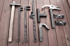 Random blacksmith tools. 3/8 round hot punch, 3/8 & 3/4 scroll wrenches, Adjustable twist wrench, role bar hardy, traditional holdfast, vise grip hold fast, and an adjustable vise mount bending fork.