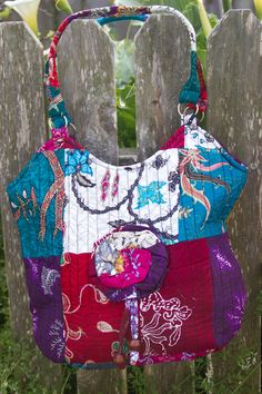Lovely handmade patchwork handbag made of Batik. Features a rosette detail with tassels and zipper closure at the top.