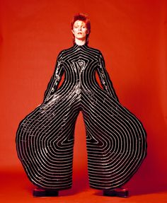 David Bowie in a striped bodysuit (glam rock). Glam rock was popular in the early Singers wore outrageous costumes and platform boots, as well as lots of glitter. Many glam rock musicians, such as David Bowie, had an androgynous appearance. Bowie Ziggy Stardust, David Bowie Ziggy, David Bowie Eyes, David Bowie Poster, David Bowie Starman, David Bowie Art, David Bowie Is Exhibition, Duncan Jones, Angela Bowie