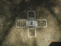 """Grafite no chão em forma de band-aids em uma vaga de carro. Destinado ao público como apenas um """"ornamento"""" à sinalização sóbria da vaga ou uma até uma possível leitura de crítica, já que o band-aid pode representar uma solução provisória e superficial, sem ser uma resolução total (possível problema do transporte urbano)."""