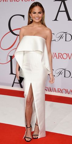 Chrissy Teigen in a white dress and Stuart Weitzman shoes.
