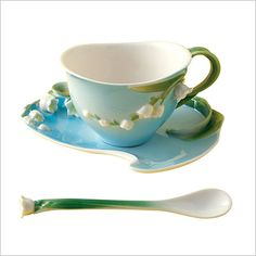 Two's Company Lily of the Valley Tea Set:   You can almost smell the enchanting scent of this delicate flower.  A soft blue background with green leaf renderings and white blossoms in hand painted porcelain.  Three piece set includes teacup, saucer and spoon. 4