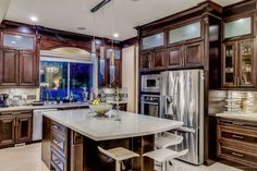Gorgeous kitchen! Dark brown cabinets with beautiful sparky white quartz counters. Three Swarovski chandeliers on top. Interior Design by @sepidehhhh_ #beautiful#shiny#classy#kitchendesign#kichen#luxurylife#luxury#interiordesign#huge#gorgeous# sophisticated#custommade#luxe#elegance#customkitchen#archeticture