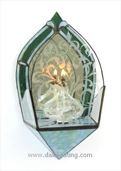 Stained glass candle holder for the wall. From the book: Candle Sconces A Step by Step Guide. The colored glass is a combination of Bullseye and Spectrum.