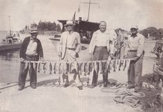 """An Alexandria Bay fishing party of the late 1940's or early 1950's shown at the upper bay included Texas pecan """"king"""" Mr. Silegman Pictured, from left, are Capt. Jack MacGregor, Mr. Silegman, his bodyguard and Capt. Joe Welsh. A Combined Boat tours vessel is behind them."""