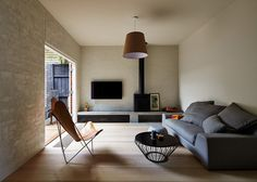 Cozy And Intimate Family House, Melbourne: Gorgeous Living Room With Grey Sofa Hanging Lamp Round Coffee Table Leather Couch TV And Small Firepit ~ joyourhome.com Architecture Inspiration