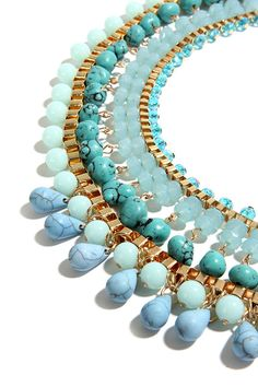 "There ain't no mountain high enough, or river wide enough, that could keep us from the River Deep Turquoise Statement Necklace! This dazzling beaded collar necklace has a plethora of stunning beads in various sizes, and shades of turquoise, aqua, mint green, and powder blue. Strands of shiny gold chain top off the look. Necklace measures 18"" around, plus 4"" extender chain. Lobster clasp closure. Man made materials."